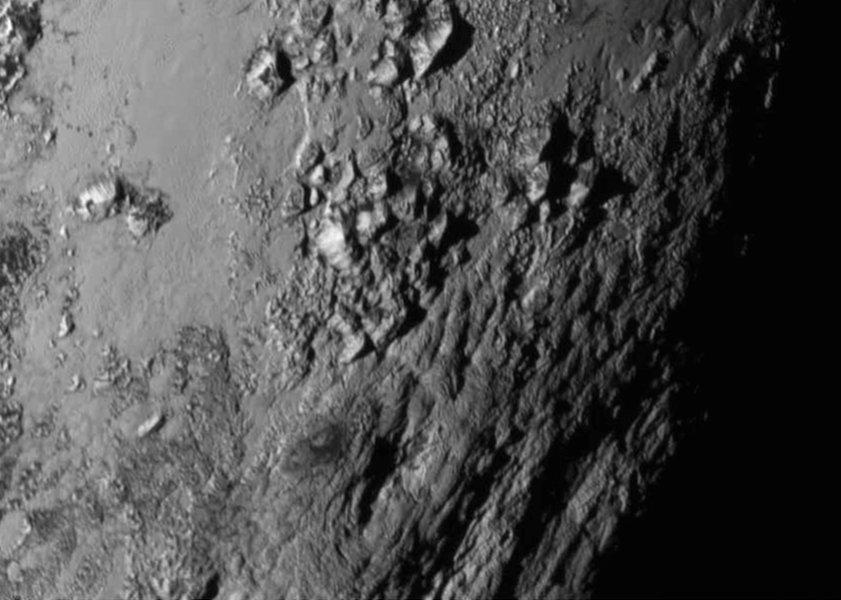 """Le montagne di ghiaccio altre 3500 metriche caratterizzano una piccola zona di Plutone, vicina al """"cuore"""" mediatico. Notiamo la superficie liscia e priva di crateri che contrasta nettamente con la zona montuosa"""