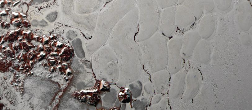 """Una splendida vista delle bolle poligonali di ghiaccio d'azoto, che evolvono lentamente (per i nostri orologi…) e ringiovaniscono la superficie dell'immenso """"cuore"""" di Plutone. Si notano anche i macigni di ghiaccio d'acqua e di metano, staccatisi dalle colline circostanti che vengono accumulati ai bordi della struttura. Fonte: NASA/Johns Hopkins University Applied Physics Laboratory/Southwest Research Institute."""