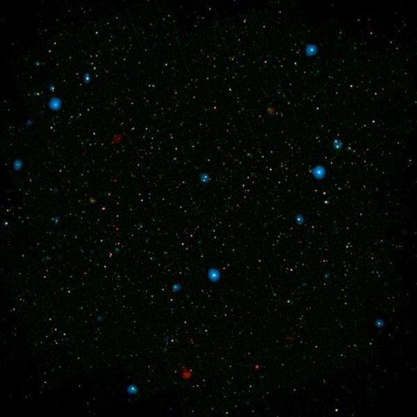 Un campo ricco di galassie. I dischetti azzurri sono quelle che possiedono un buco nero supermassiccio che emette raggi X ad alta energia. NuSTAR ne ha individuati 32 e centinaia in altri campi sparsi per tutto il cielo. Fonte: NASA/JPL-Caltech