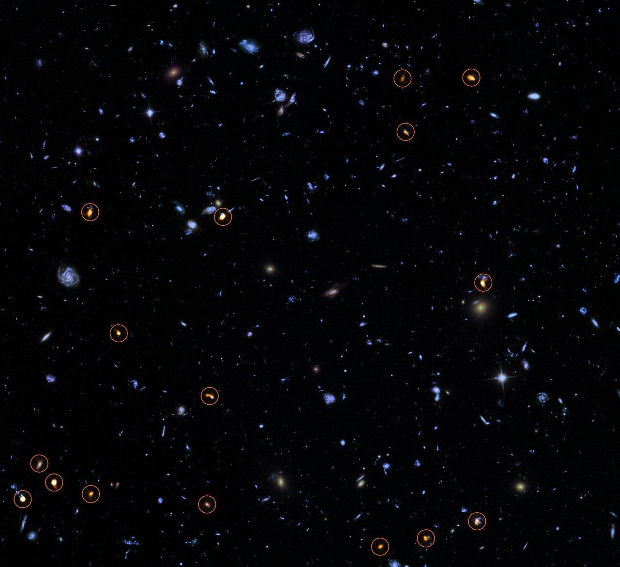 """L'HUDF con l'aggiunta delle osservazioni ALMA. Le """"sue"""" galassie sono quelle arancioni e segnate dal cerchietto. Fonte: ALMA (ESO/NAOJ/NRAO)/NASA/ESA/J. Dunlop et al. e S. Beckwith (STScI) e HUDF Team."""