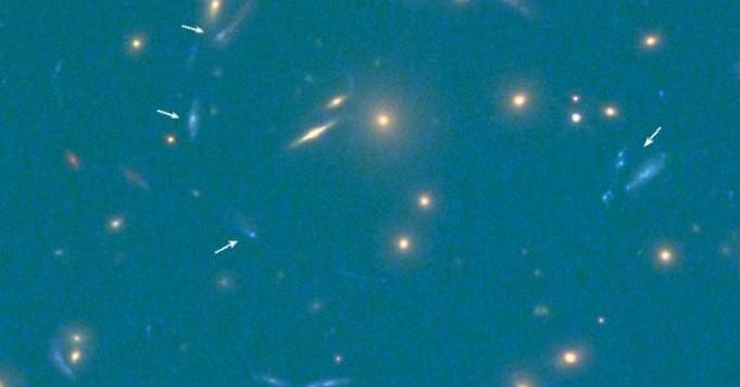 Le immagini multiple della nuova galassia ultra luminosa sono indicate dalle frecce bianche. Fonte: IAC e HST
