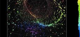 Come si creano e si identificano flussi neutrinici negli esperimenti. Un'interazione del neutrino-elettrone osservata nell'esperimento TK2. Il neutrino interagisce con una molecola d'acqua producendo un elettrone che a sua volta emette luce Cherenkov mentre attraversa il il rivelatore. Questa luce è immagazzinata dai fotosensori e trasformata in un segnale elettrico visibile. Fonte: Albert Einstein Center for Fundamental Physics (AEC), Laboratory for High Energy Physics.