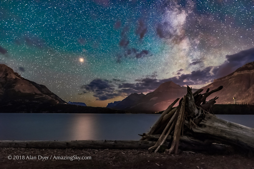 Bright yellow Mars approaching a close opposition in July 2018 shines over the waters of Middle Waterton Lake in Waterton Lakes National Park in southwest Alberta on the Alberta-Montana border. Mars is so bright it produces a glitter path on the water. The Milky Way is at right. This was from Driftwood Beach, windy as always this night. The sky is tinted green with bands of airglow, though there was a dim aurora to the north this night as well, quite unexpected. Waterton Lakes is a World Heritage Site and a Dark Sky Preserve. This is a stack of ten exposures for the ground to smooth noise (and blur the wind-rippled water) at f/3.2, and a single exposure for the sky at f/2.2, all 30 seconds with the Sigma 24mm Art lens and Nikon D750 at ISO 6400. Taken July 11/12, 2018 at the end of a 6-hour session training the Dark Sky Guides staff. It was a superb night, with everything to see in the sky.