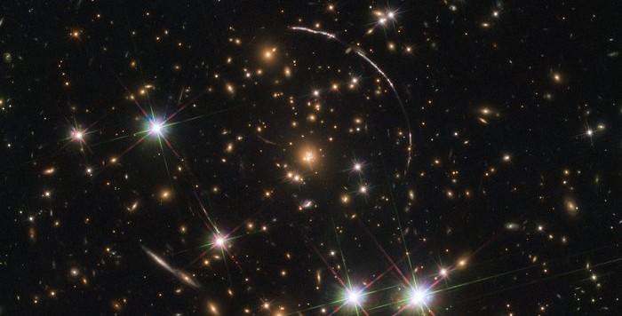 Gli archi galattici ci inviano la luce che ci arriva dopo 11 miliardi di anni e che è stata inviata verso di noi grazie all'effetto lente gravitazionale.  Essi sono tra i più luminosi mai osservati. Fonte: ESA/Hubble, NASA, Rivera-Thorsen et al.